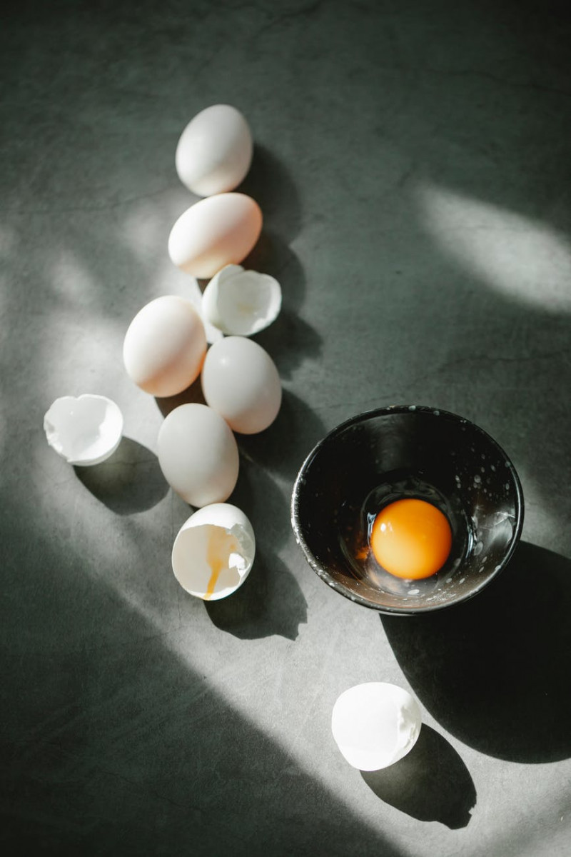 pile of eggs and shells scattered on table near bowl with raw yolk