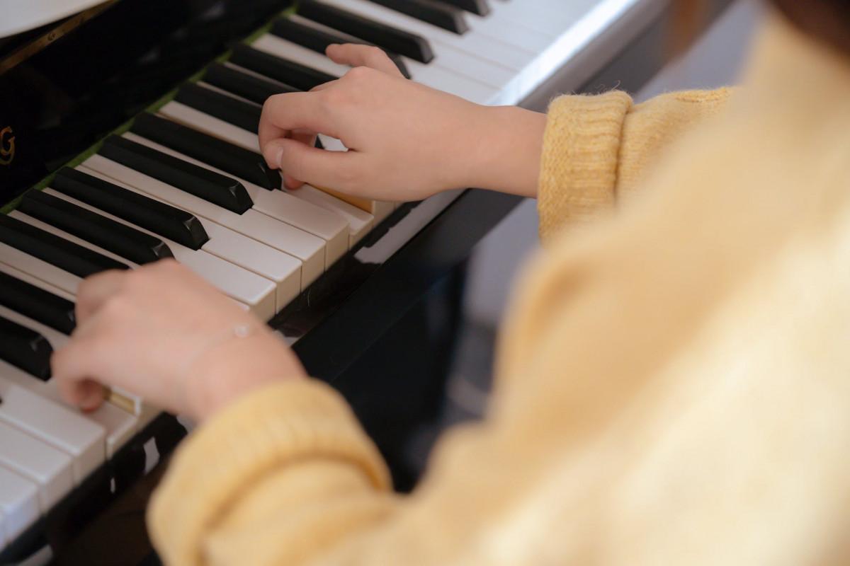 woman in yellow sweater playing piano