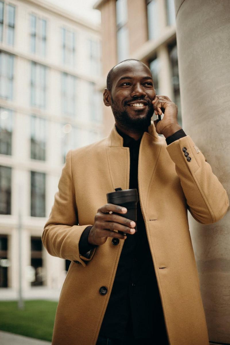 man wearing brown jacket using smartphone while using smartphone