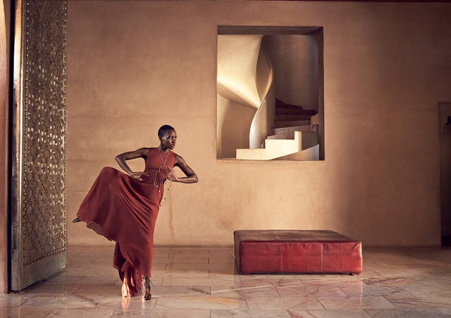 Nyong'o in the entrance hall of Marrakech's exclusive Ksar Char-Bagh resort, a chic retreat tucked away in the city's palm grove. Vera Wang Collection copper trapeze dress.
