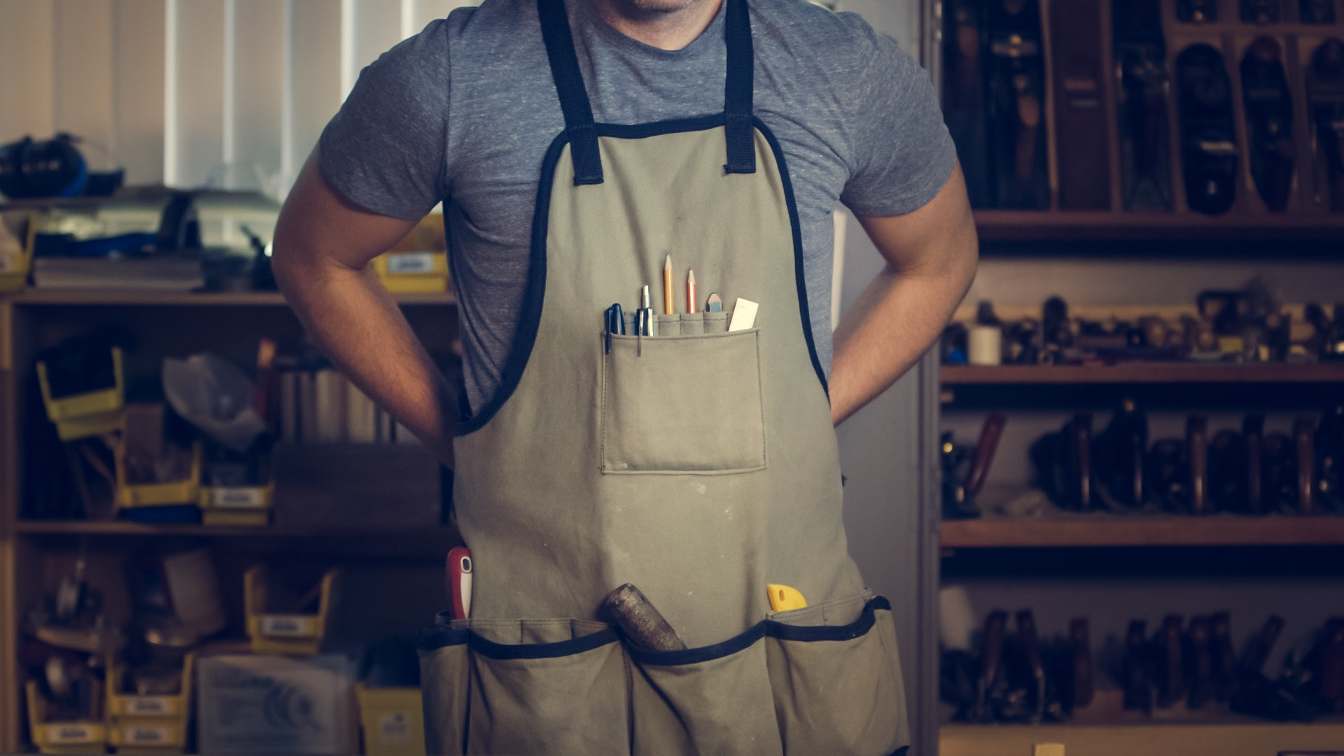A man standing in steel workshop and wearing tool pouch.