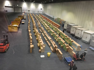 a loading dock with hundreds of boxes stacked three high in five rows more than 50 metres long each