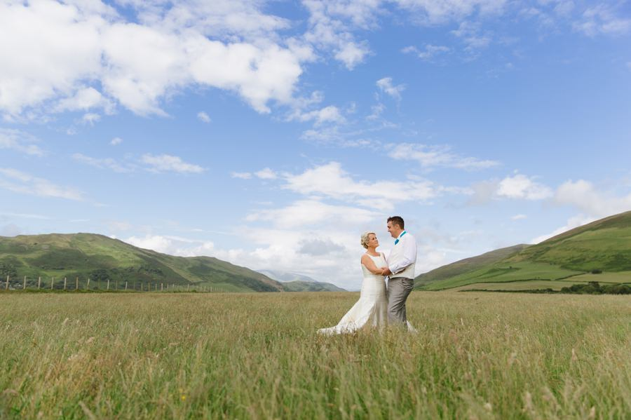 bride and groom in grass field. Get married in North Wales