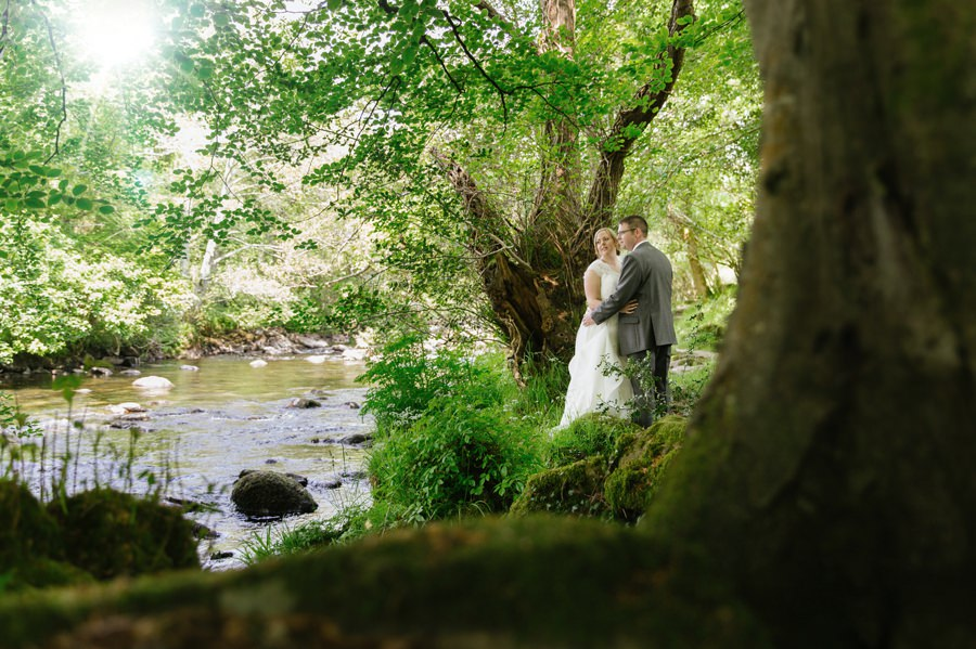 bride and groom near river in Criccieth. Get married in North Wales