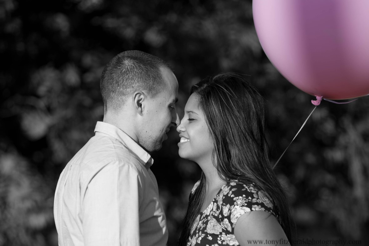 smiling expecting parents and pink balloon
