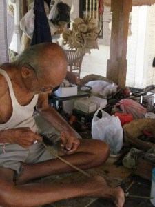 I Wayan Tangguh at work weaving horse hair into strands for masks.