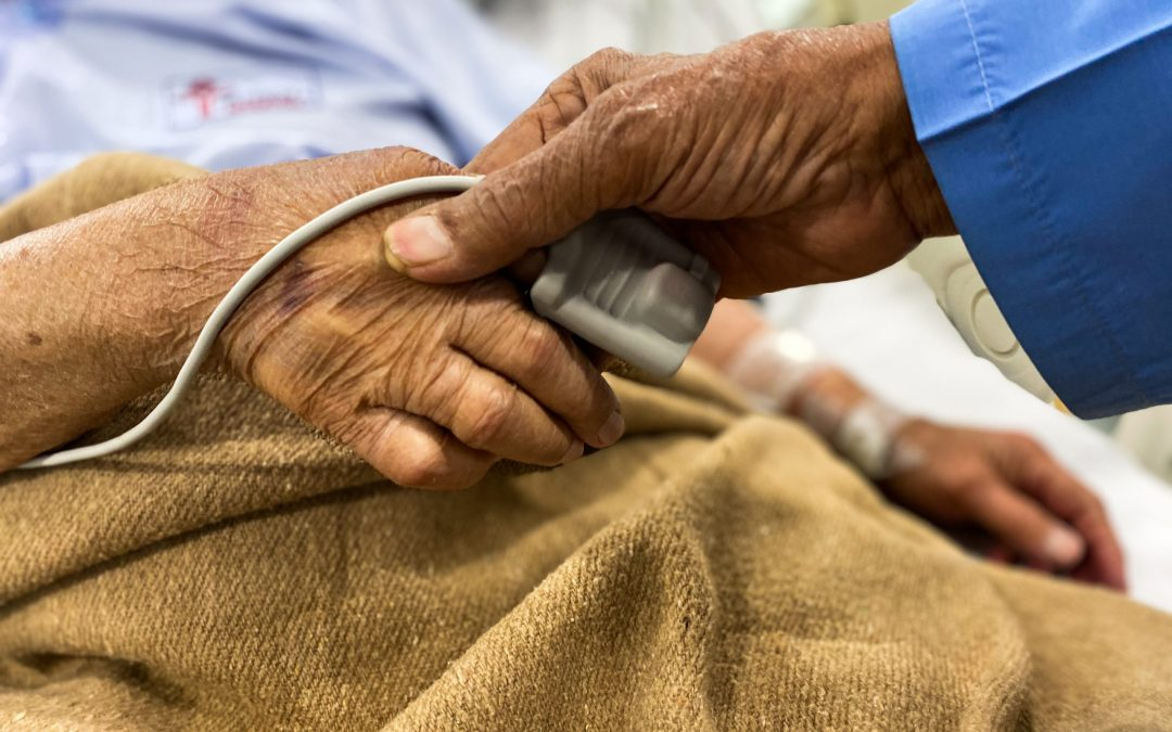 An elderly couple hold hands. One is lying in a hospital bed with an oxygen meter on their finger.