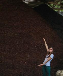 Daniela Uribe stands near a mound of cascara.