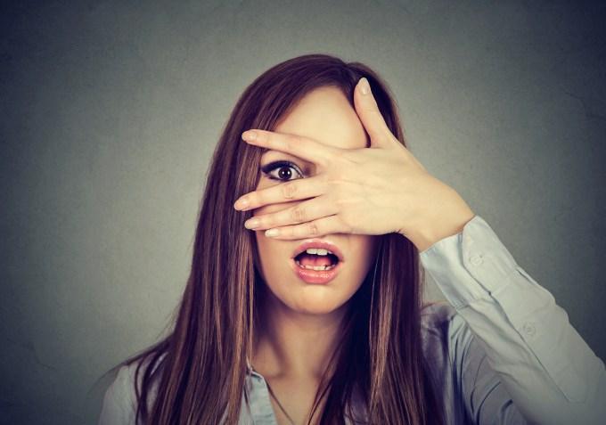 afraid-woman-peeking-through-her-fingers