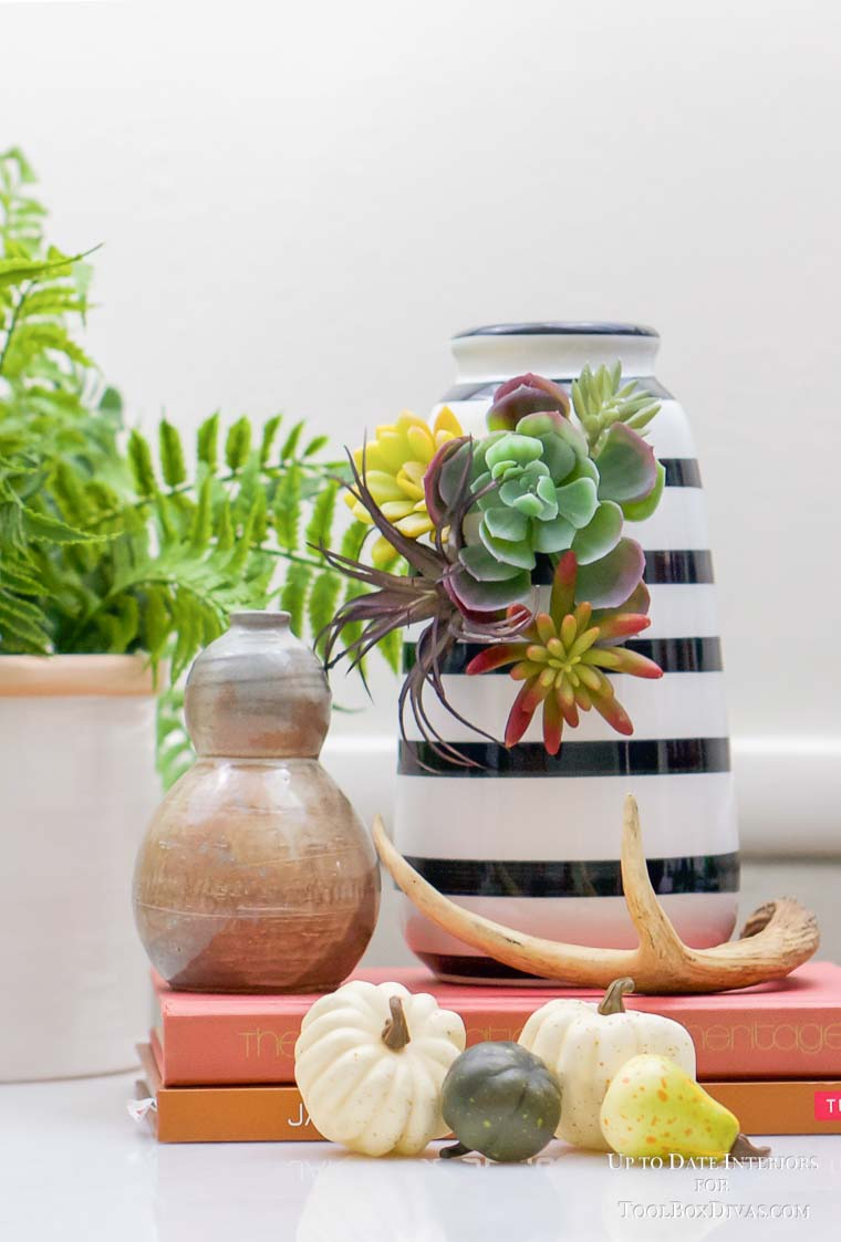 striped vase with orange books and antlers for fall decor