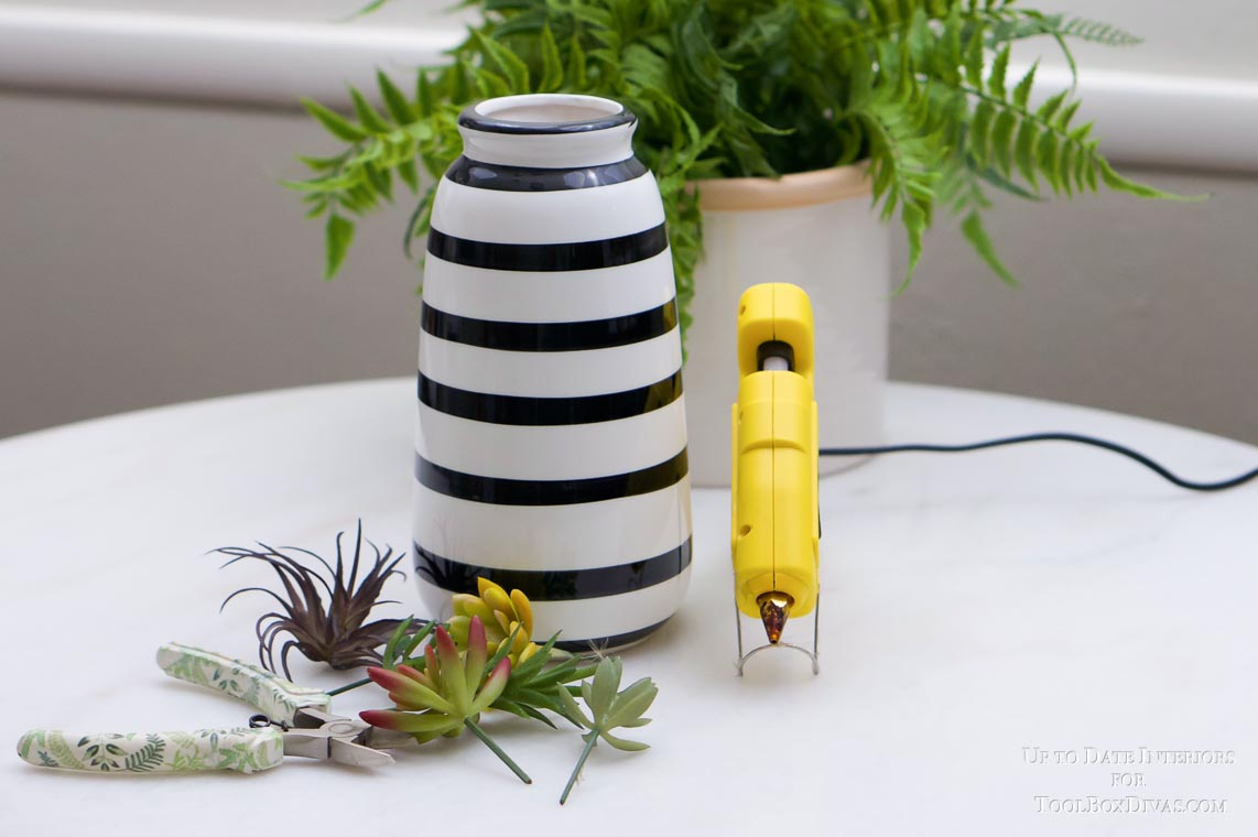 white and black striped vase with yellow hot glue gun, plant, and succulents