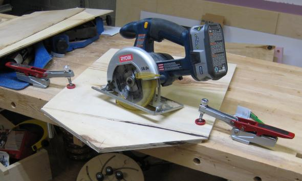 Craftsman hold down peg clamps securing plywood for sawing