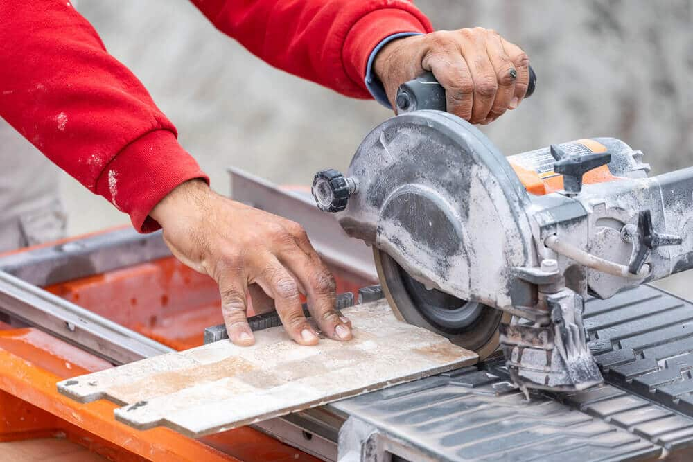 Worker Using Tile Saw to Cut Tile