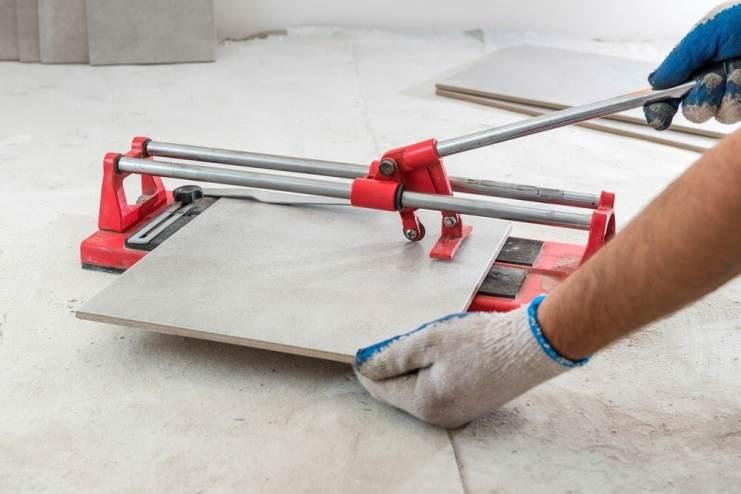 Tiler uses manual tile cutter