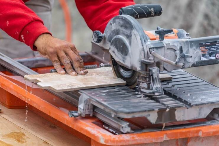 Worker Using Wet Tile Saw to Cut Tile At Construction Site