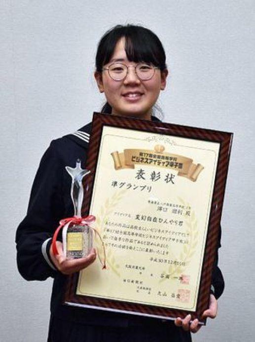 表彰状とトロフィーを手に喜ぶ澤口さん