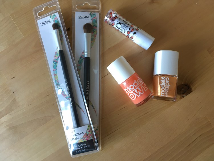 Picture of eye make up brushes, nail polish and a lipstick