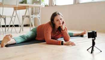 woman in red knit sweater and green pants sitting on brown wooden table