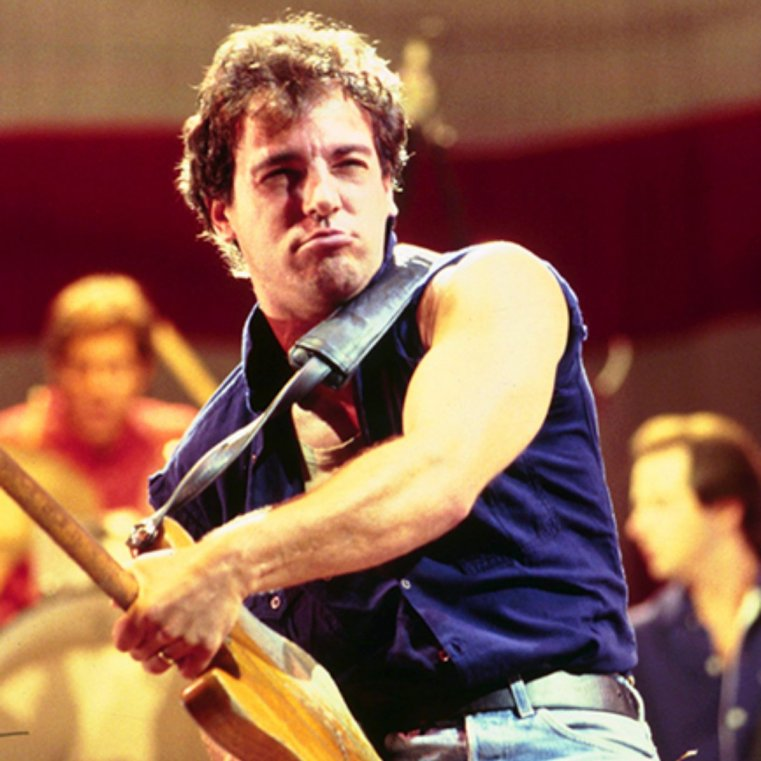 Bruce Springsteen playing guitar on stage circa 1980s
