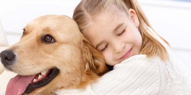 little girl hugging a dog