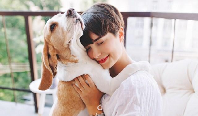 woman snuggling dog