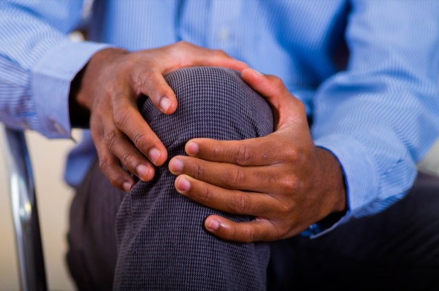 hands of a man making a massage on his knee, pain