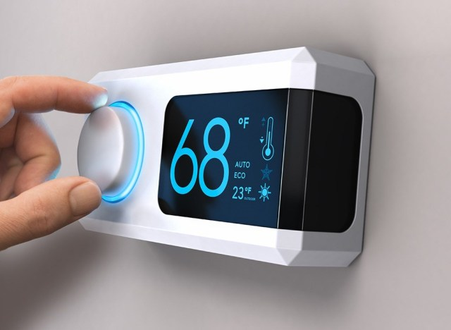 Woman setting thermostat