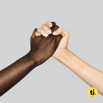 A white an a black hand holding each other to symbolize color-blind diversity
