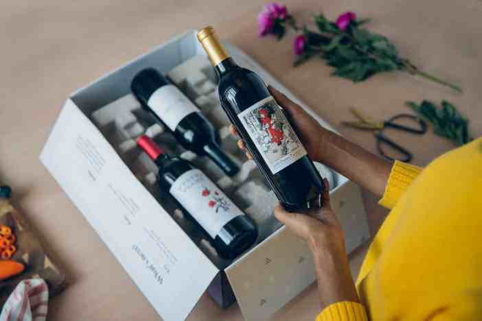 A wine subscription box opened with three bottles of wine to entice customers