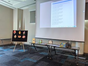 Naperville Public LIbrary Meeting Room set up for Family Storytime (projector screen pulled down, tables below screen with books and puppets, a flannel board off to the left for flannel stories)