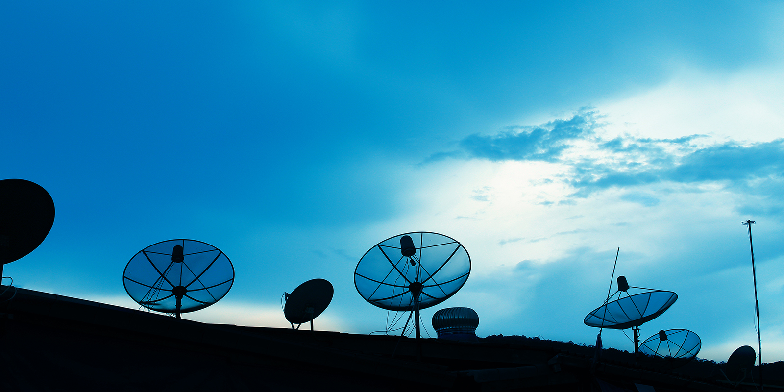 A picture of a blue sky with satellite disks on a dark surface at the bottom on the science PR agency page.