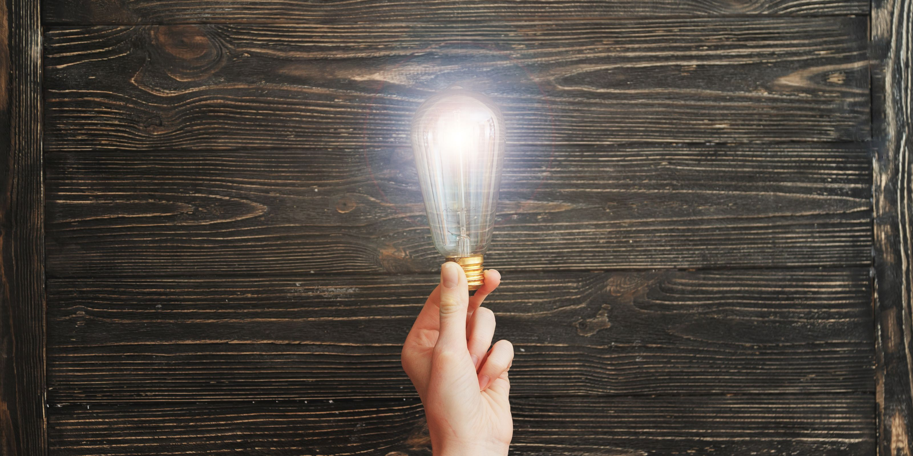 A picture of someone's hand holding a bright light bulb with a wooden background on the energy PR agency page.