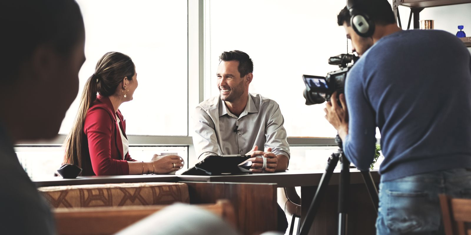 Image of man and woman chatting at desk while being filmed by cameraman for B2B video production company page