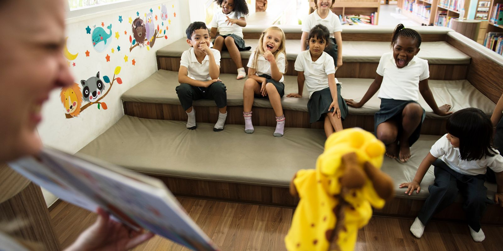 A picture of young school children sitting in a classroom on soft mats whilst their teacher does a puppet show, on the educational video production page.