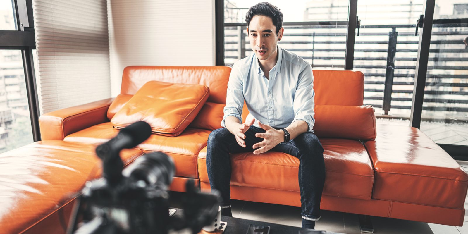 A picture of a man being filmed doing an interview whilst sat on an orange sofa on the product demo video production page.