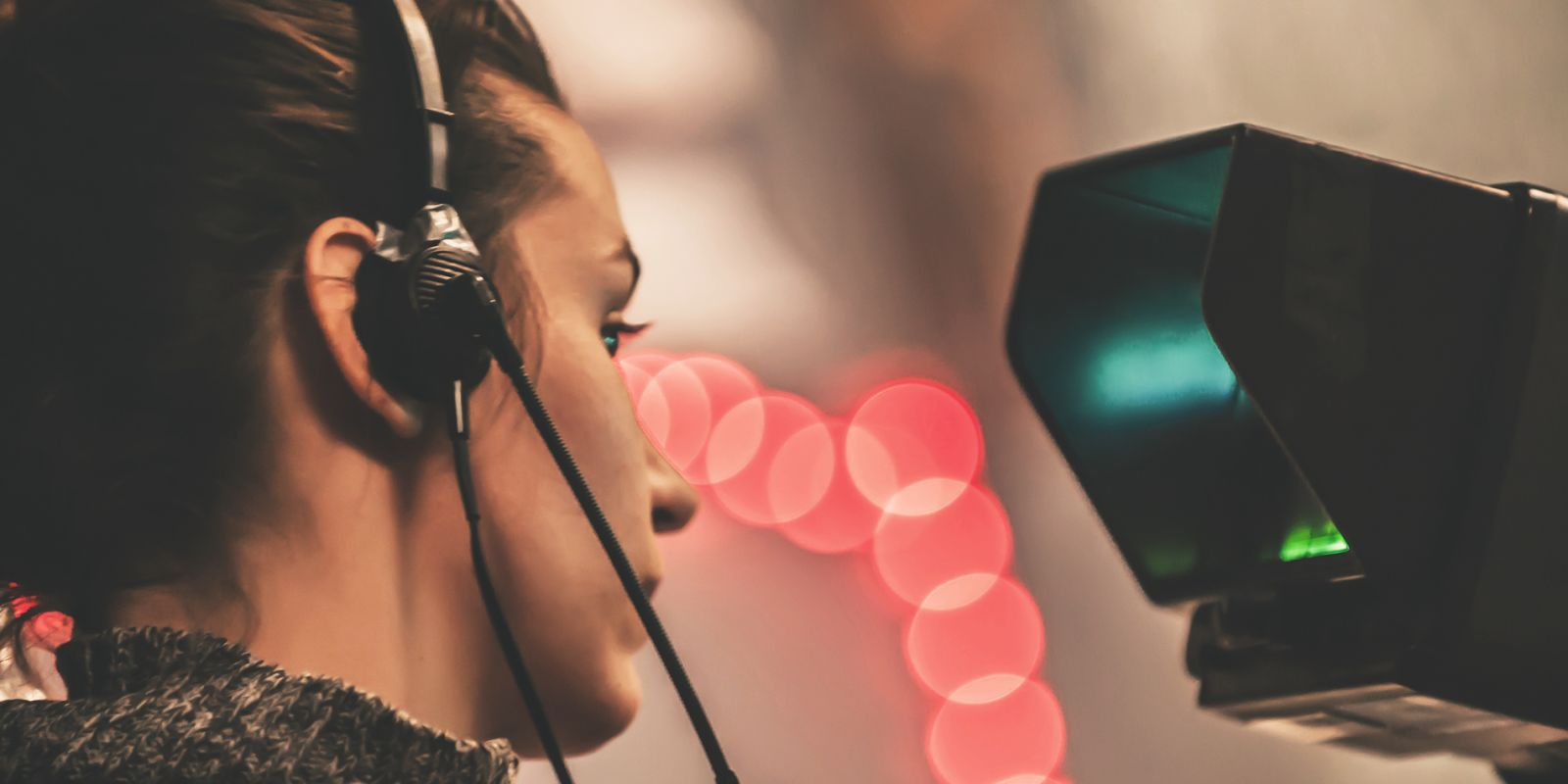 A close up picture of a woman with a headset on looking at the screen of a video camera with blurred lights in the background on the recruitment video production page.