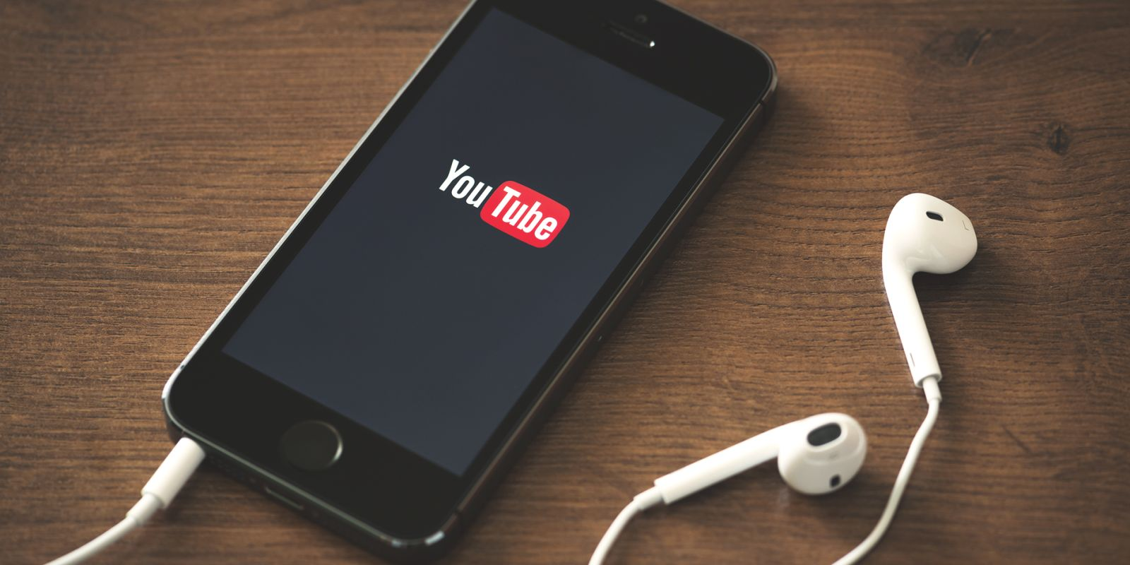 A picture of a phone with the YouTube app open and a set of earphones plugged in on the social video strategy page.