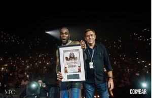 Burna Boy with plaque at SSE Arena