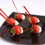 five red crystal skewers on strawberries coated in white chocolate