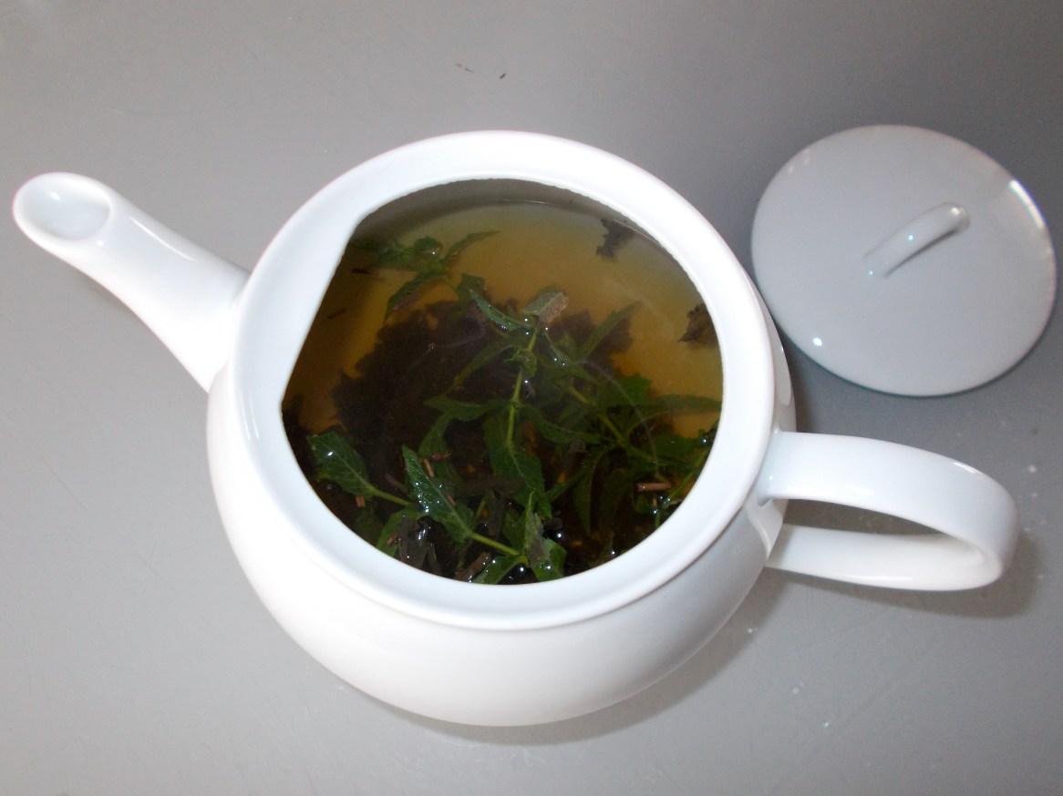 on rajoute de l'eau frémissante sur le thé avec les feuilles de menthe et le sucre