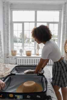 african american woman putting luggage in suitcase
