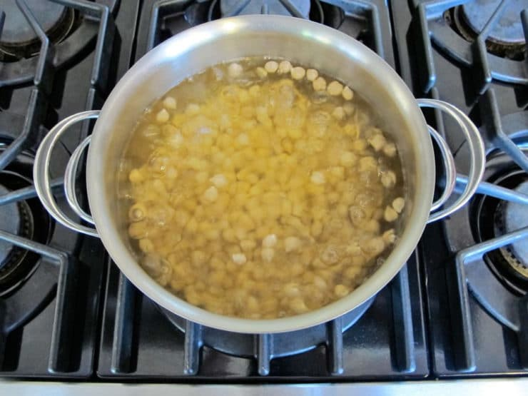 Simmering chickpeas in large pot on stovetop.