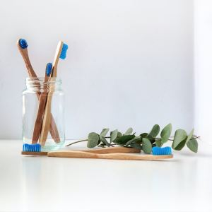 blue and white toothbrush in clear glass jar