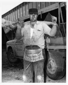 Worker showing broken glass at a Newmarket shopping plaza attacked by the strikers. Photo by Drew. June 22, 1961. York University Libraries, Clara Thomas Archives and Special Collections, Toronto Telegram fonds, ASC53008.