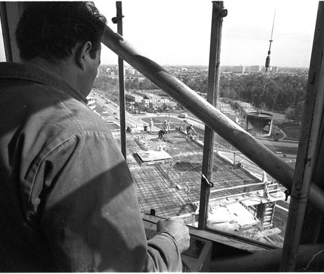 Crane operator in his cabin hoisting a concrete bucket. Photo by Dick Loek. October 2, 1968. York University, Clara Thomas Archives and Special Collections, Toronto Telegram fonds, ASC52559.