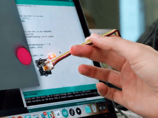 A hand holding a lighted stylus that is programmed by a computer
