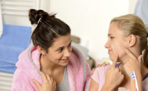 female showing friend her pimple