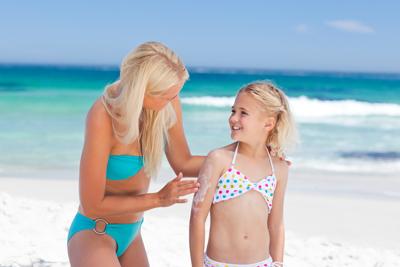Mother applying sun cream on her daughter's back