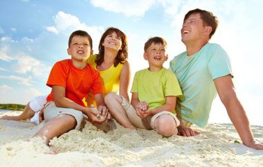 Photo of happy family sitting on sand during summer rest