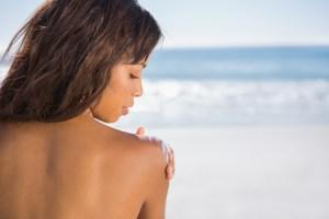 Woman on the beach applying sun cream on her shoulder